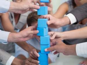 88586374-co-workers-building-with-blocks-gettyimages